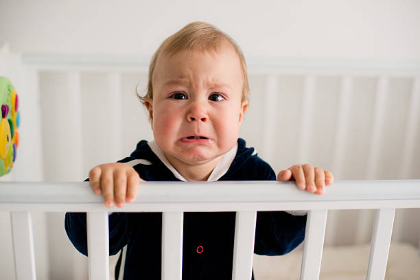 baby crying in the crib stock photo
