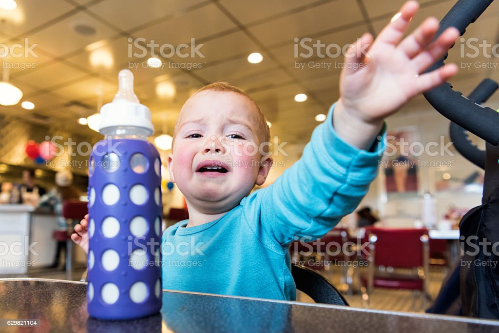 Baby crying near his baby bottle stock photo