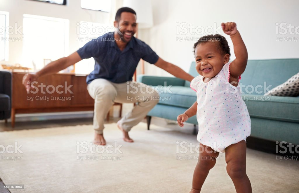 Baby Daughter Dancing With Father In Lounge At Home stock photo