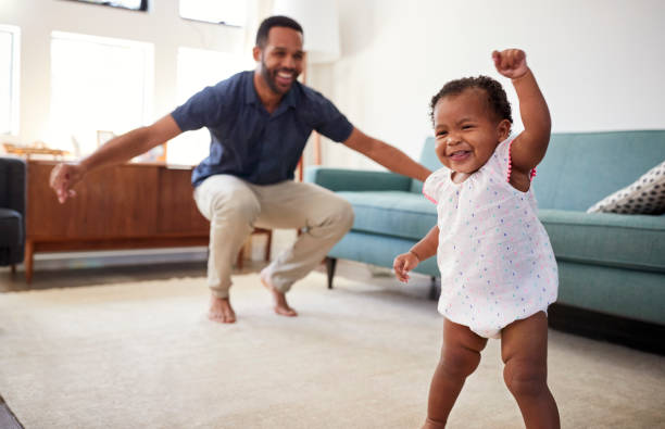 baby daughter dancing with father in lounge at home - first step stock photos and pictures