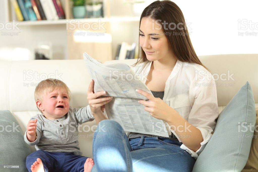 Baby demanding attention and mother ignoring him stock photo