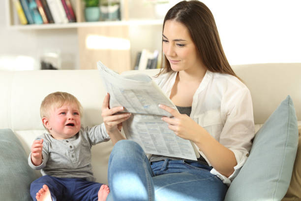 Baby demanding attention and mother ignoring him Baby crying demanding attention and his mother ignoring him sitting on a couch in the living room at home ignoring stock pictures, royalty-free photos & images