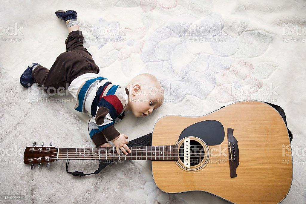 Baby Discovering the Guitar stock photo