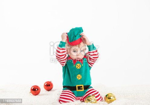 Xmas joy. Playful baby elf helping to decorate Christmas tree with colorful balls, empty space