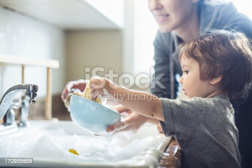A cute toddler aged boy wearing a blue diaper and tshirt helps out with with washing the dishes, standing on a chair to be able to reach the sink full of soapy bubbles and dishes.  His mother smiles behind him as she supervises his sensory perception experience. Bright sunlight comes in through the window behind him, lighting the sparse modern kitchen.