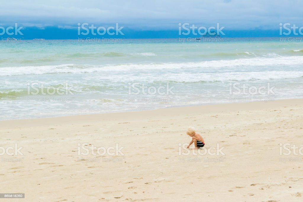A baby drawing on the sand at the bech alone, stock photo