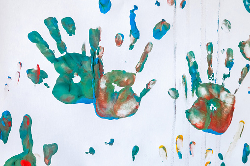 Baby drawing with watercolor on white wall background