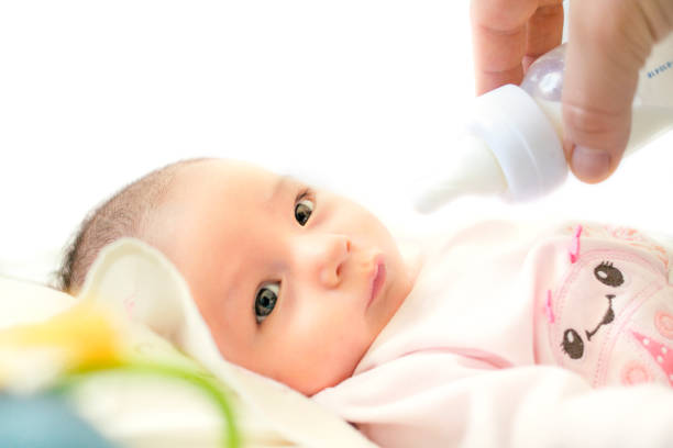 baby drinking breast milk or baby food with feeding bottle stock photo