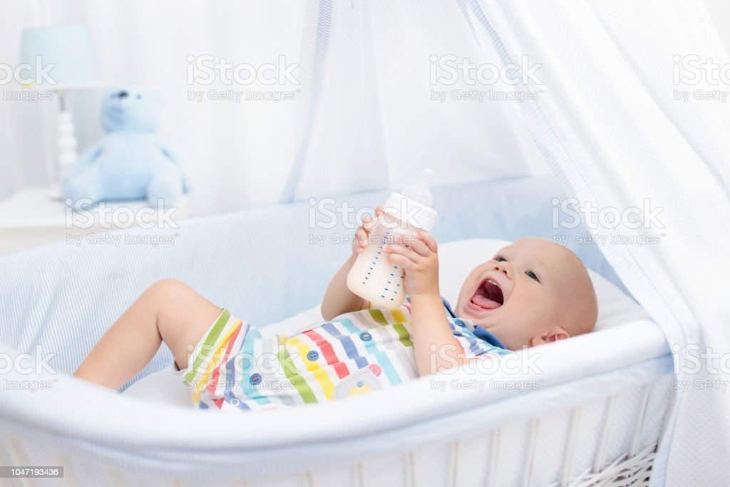 Baby consumptiemelk. Jongen met formule fles in bed foto