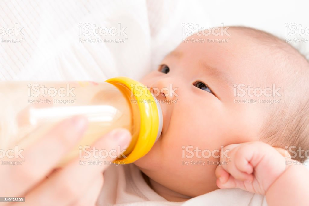 Baby drinking milk in a baby bottle stock photo