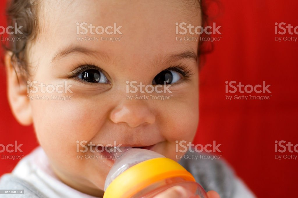 Baby drinking milk out of a bottle royalty-free stock photo