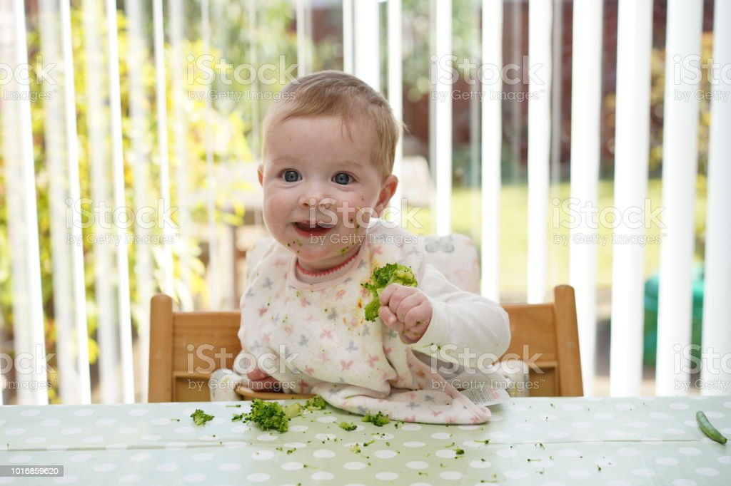 Bebé comiendo brócoli - Foto de stock de Alegre libre de derechos