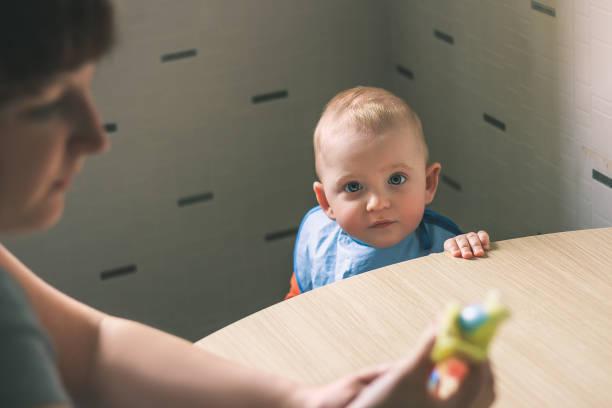 baby essen in der küche. mutter wird das kind zu ernähren. baby ernährung. - kinderstuhl und tisch stock-fotos und bilder