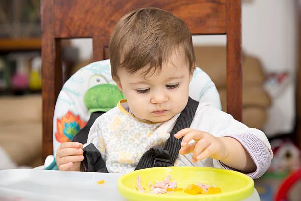 baby essen aus einer platte - kinderstuhl und tisch stock-fotos und bilder