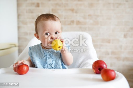 istock Baby eating fruit. Little girl biting yellow apple sitting in white high chair in sunny kitchen. Healthy nutrition for kids. Solid food for infant. Snack or breakfast for young child 1141697595