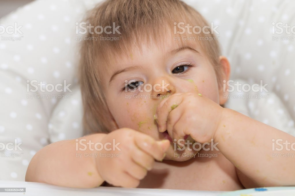 Messy And Dirty Sweet Baby Is Eating Avocado With Hands. Portrait...