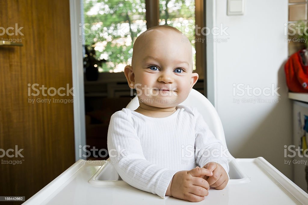 Baby Eating in High Chair stock photo