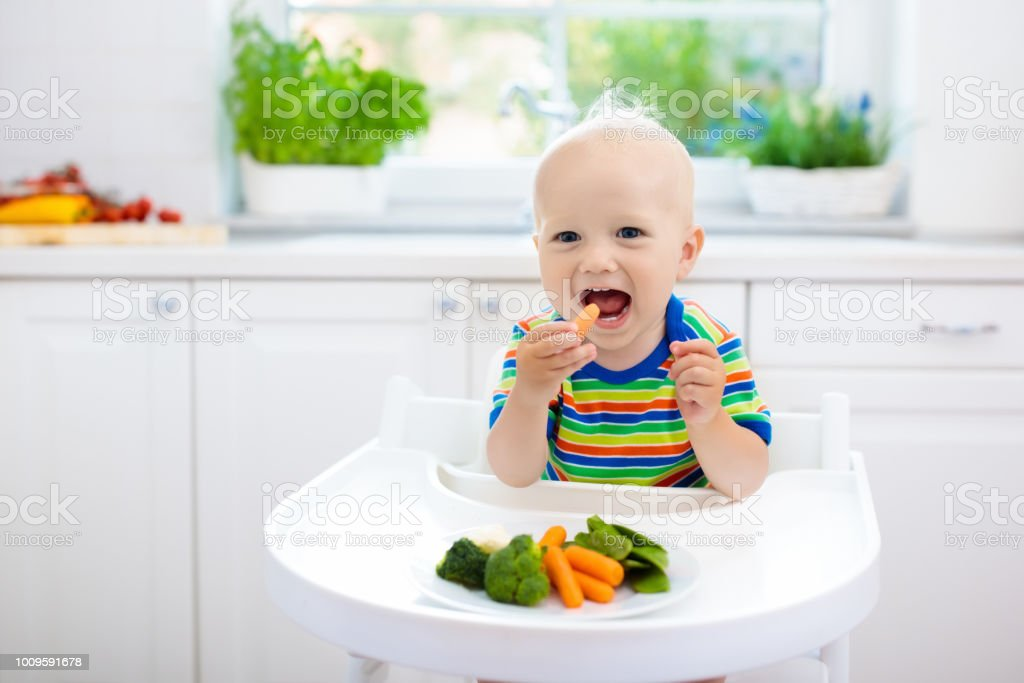 Baby eating vegetables in kitchen. Healthy food. stock photo