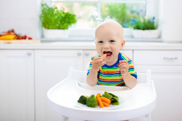 baby eating vegetables in kitchen. healthy food. - nutrire foto e immagini stock