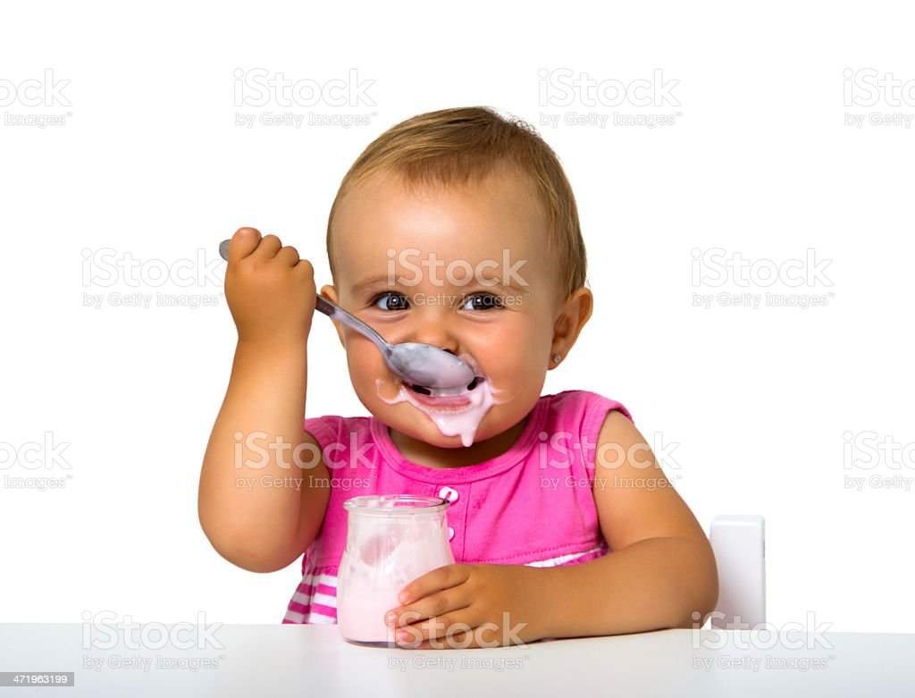 A baby eating yogurt from a jar, mostly missing their mouth stock photo