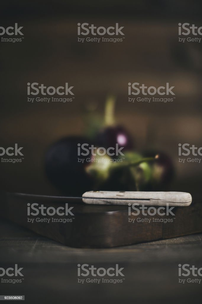 Baby eggplant on chopping board with knife stock photo
