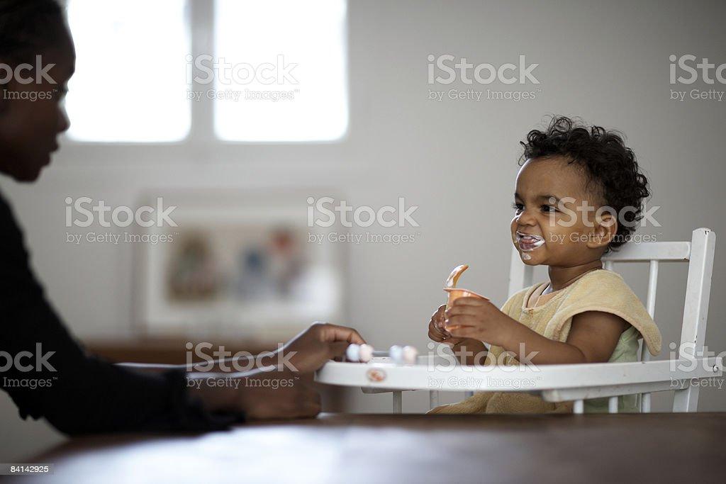 baby feeding himself yoghurt royalty-free stock photo