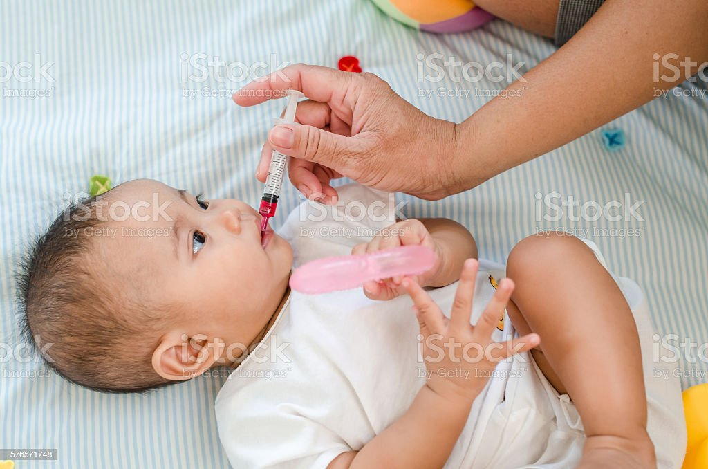 Baby feeding with liquid medicine stock photo