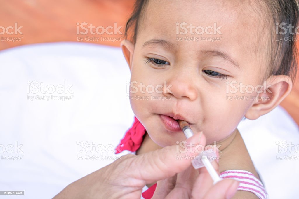 Baby feeding with liquid medicine with a syringe stock photo