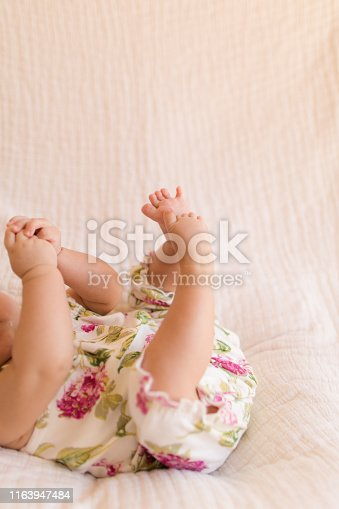 18-week-old baby girl hands, legs, toes and feet. Baby learning to grab feet with hands. Baby sucking fingers.
