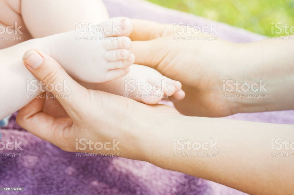 Baby feet in mother hands. Tiny newborn baby feet, concept of happy family. Fake color tone of photo stock photo