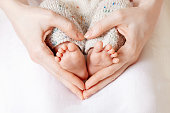 istock Baby feet in mother hands. Tiny Newborn Baby's feet on female Heart Shaped hands closeup. Mom and her Child. Happy Family concept. Beautiful conceptual image of Maternity 1206221259