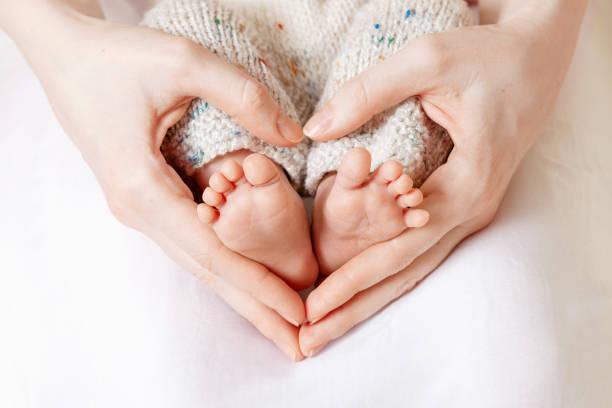babyfüße in mutterhänden. winzige neugeborene baby füße auf weiblichen herzförmigen händen nahaufnahme. mama und ihr kind. happy family konzept. schönes konzeptbild von mutterschaft - baby stock-fotos und bilder