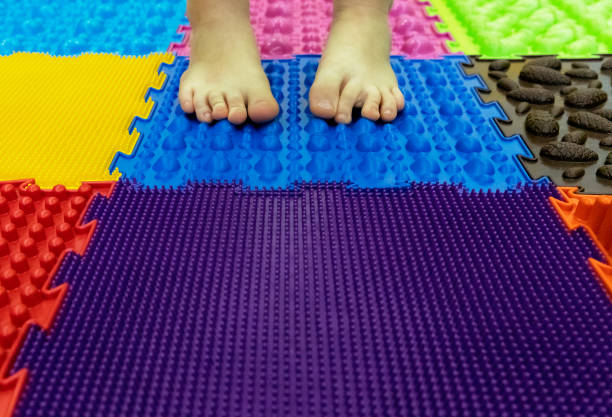 baby feet on a special orthopedic carpet. background - percezione sensoriale foto e immagini stock