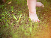 Baby feet on the green grass with sun light.