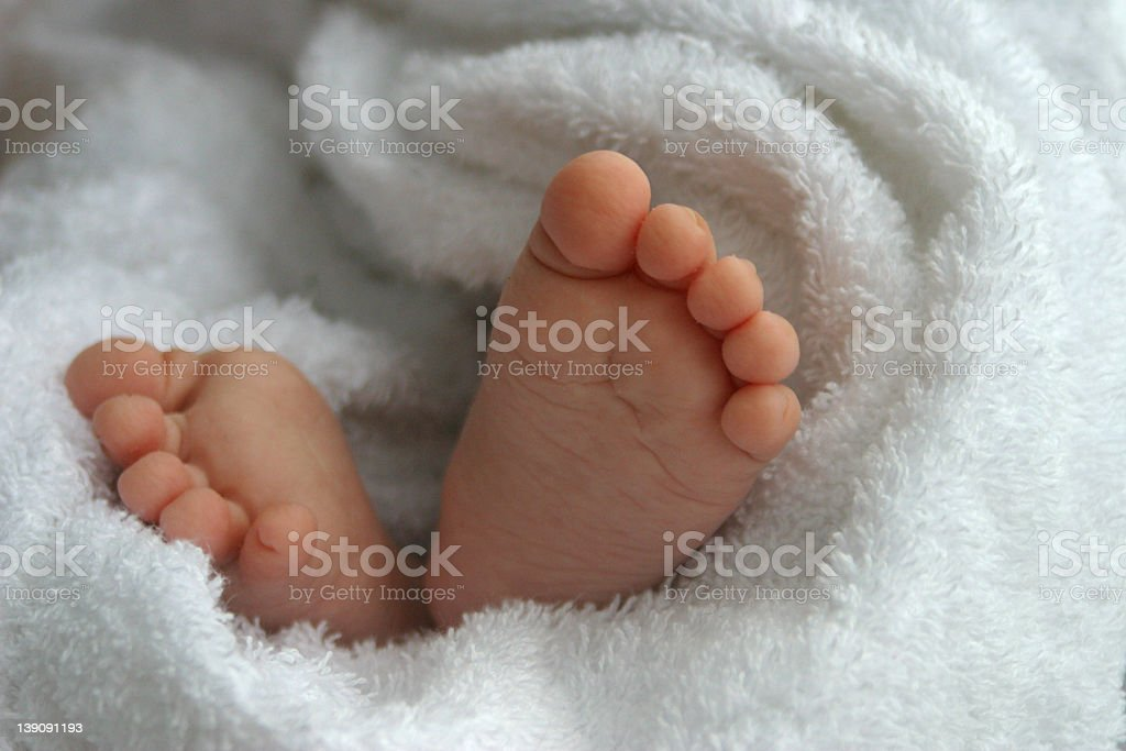 Baby feet wrapped in a fluffy white towel royalty-free stock photo