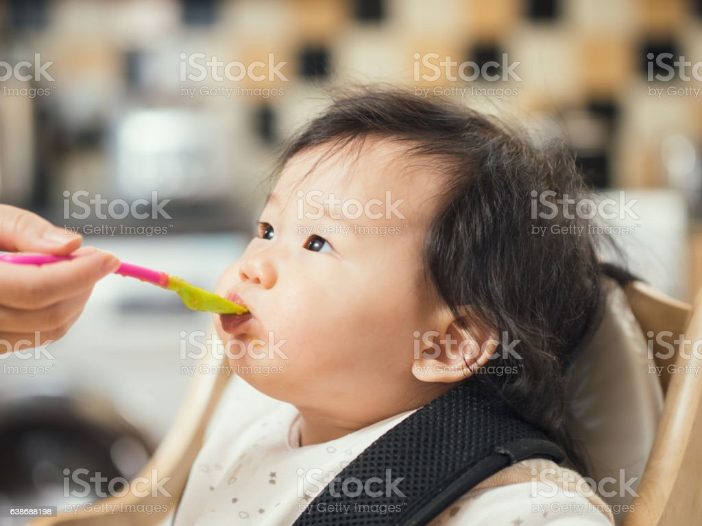 baby first weaning on high chair stock photo