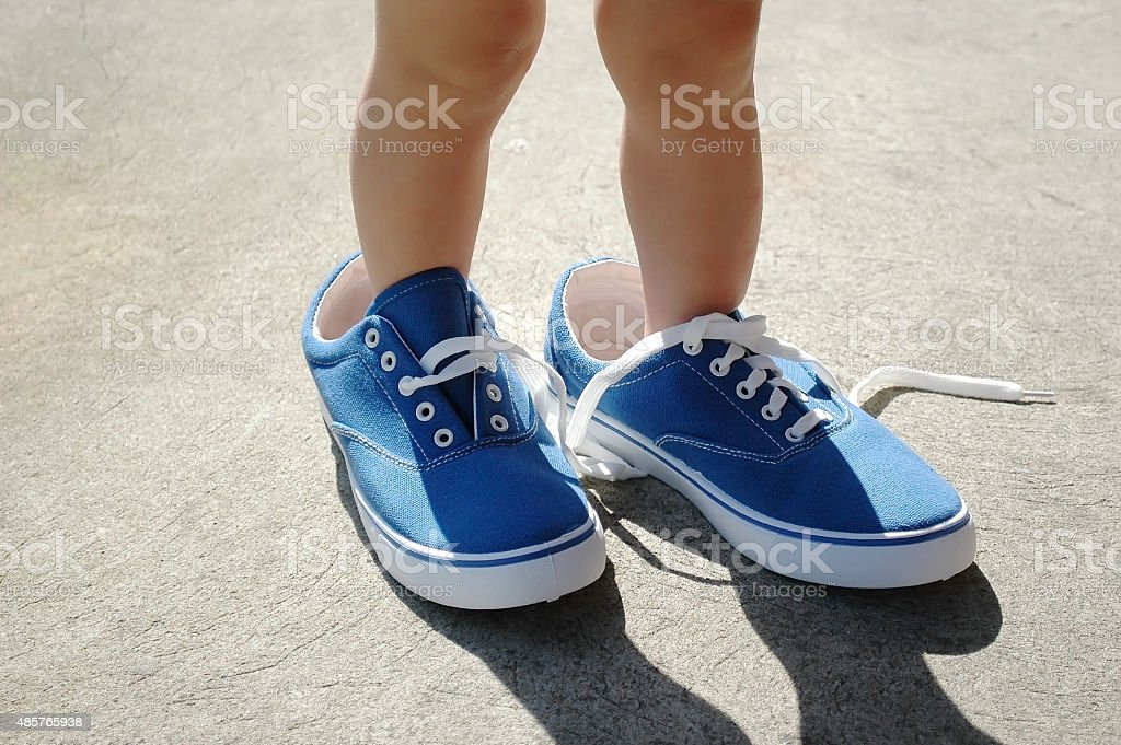 Baby foot stepping into big shoes to fill. stock photo