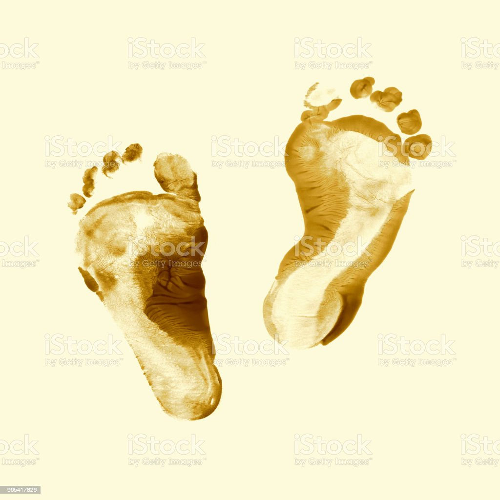 Baby footprints. Golden fingerprint or stamp texture artwork of kids. Top view. Close up. stock photo