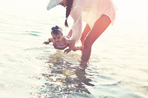 Baby zum ersten Mal im Meer – Foto