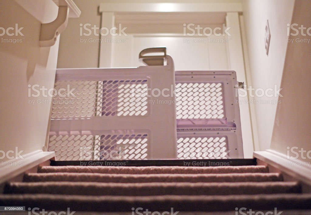 Baby gate view from basement with carpet stairs stock photo