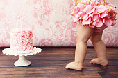 A one year old baby girl stands beside her pink birthday cake. Cropped image.