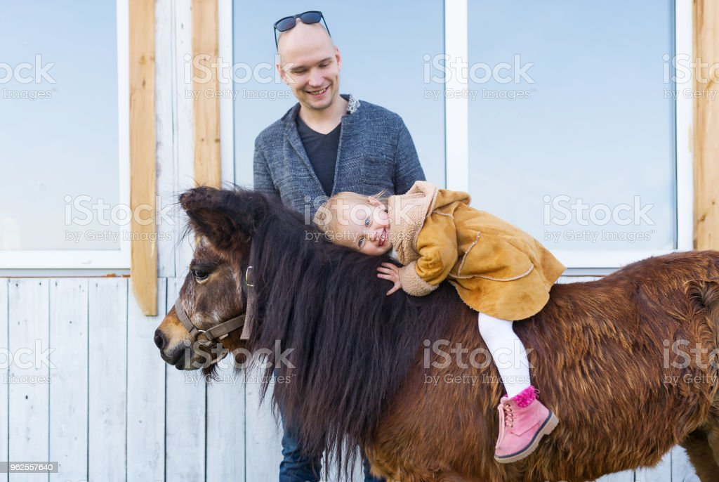 Baby girl and her best friend brown pony. Happy father and her little horsewoman. stock photo
