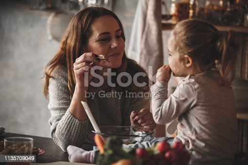 istock Baby girl and her mother eating vegetables while preparing meal 1135709049