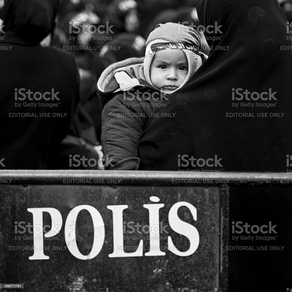 Baby Girl Behind Police Barrier stock photo