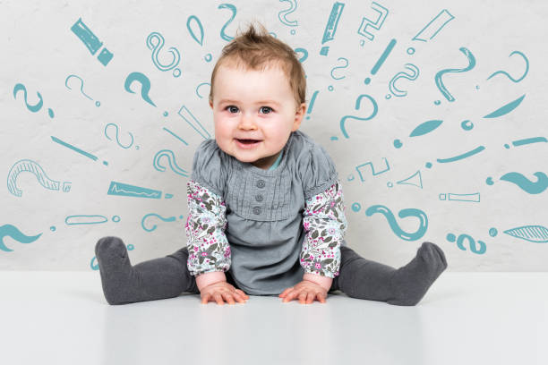 Baby girl being overwhelmed shown by question and exclamation mark graphics around head stock photo
