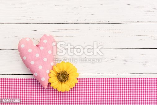 591421282 istock photo Baby girl birthday greeting card background with pink heart and blossom 898911380