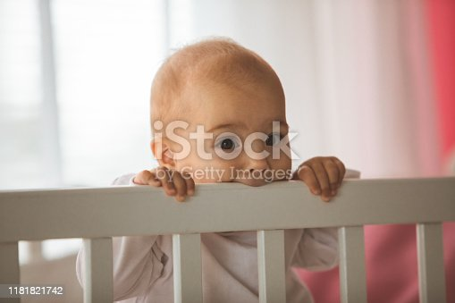 Close up of portrait baby girl biting a edge of crib and looking at camera.