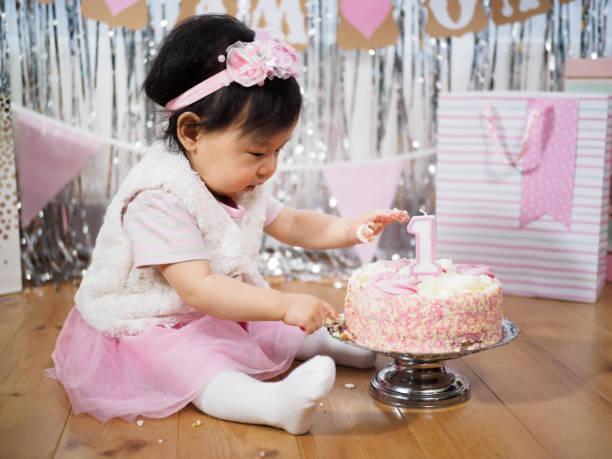 babymädchen feiern ihren ersten geburtstag - nummer 1 kuchen stock-fotos und bilder