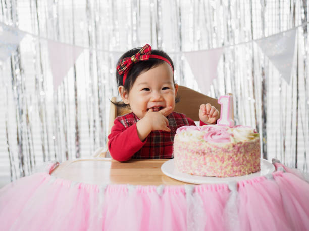 baby girl celebrate her first birthday front view of baby girl celebrate her first birthday first birthday stock pictures, royalty-free photos & images