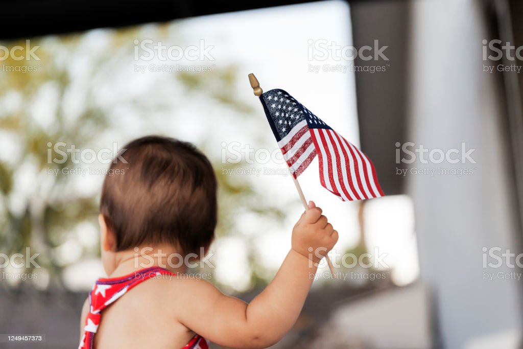 Baby girl celebrating  4th of July with USA flag in hand, Traditional American Holiday Baby girl celebrating  4th of July with USA flag in hand, Traditional American Holiday, selective focus - Image Arm Stock Photo